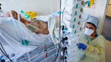 Une soignante s'occupe d'un patient atteint du Covid-19 dans l'unité de soins intensifs de l'hôpital privé l'Estrée, le 12 novembre 2020 à Stains, près de Paris