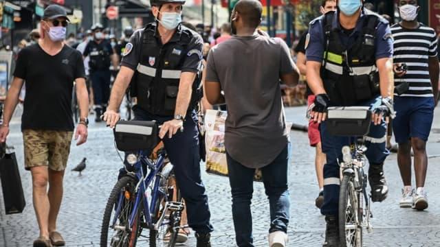 Des agents vérifient que le port du masque obligatoire est respecté, rue Montorgueil, le 15 août 2020 à Paris