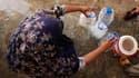 Une femme remplit des bouteilles avec de l'eau potable, dans un hôpital de campagne, à Nowshera, dans le nord-ouest du Pakistan. Les inondations provoquées dans le pays par des pluies de mousson diluviennes ont fait plus de 1.600 morts, 2 millions de sans
