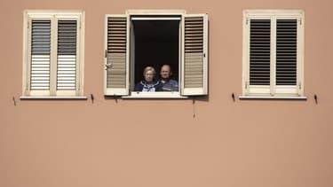 Image d'illustration - Deux personnes regardant dehors depuis leur fenêtre - Tiziana FABI / AFP