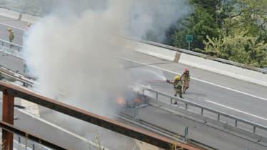 Des pompiers suisses intervenant sur une Model S en feu après un accident.