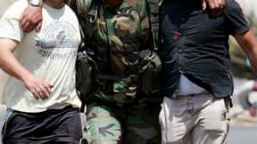 Des civils au secours d'un soldat libanais blessé dans le village d'Adaïsseh, au Sud-Liban. Un journaliste libanais et trois soldats libanais ont été tués lors d'un incident qui a opposé des militaires libanais et israéliens dans ce village. /Photo prise