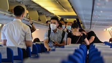 Des passagers, portant des masques, embarquent à l'aéroport international de Pudong à Shanghai pour un vol à destination de Wuhan, le 14 juillet 2020