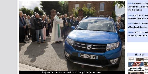 Le père Zacharie bénit la nouvelle voiture de la paroisse, une Dacia Sandero bleue.