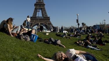 Des Parisiens prennent le soleil non loin de la tour Eiffel, dimanche 9 mars.
