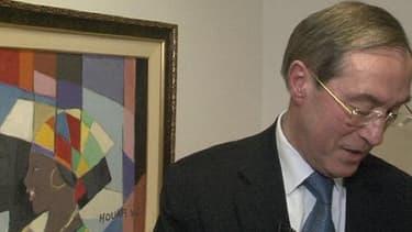 Claude Guéant, ancien ministre de l'Intérieur sous Nicolas Sarkozy, dans son bureau d'avocat en présence du tableau offert qui crée la polémique.