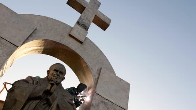 Des ouvriers d'origine russe travaillent à l'installation d'une statue géante du pape Jean-Paul II, le 28 novembre 2006 à Ploërmel.