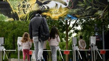 Deux fillettes accompagnées de leur père arrivent au parc zoologique de Vincennes, le 8 juin 2020 à Paris