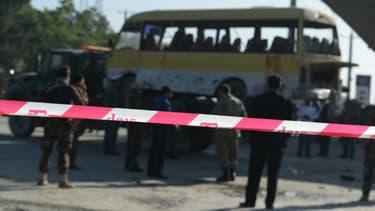 Le 20 juin 2016, en Afghanistan, des policiers positionnés devant la scène d'un attentat-suicide contre un bus, à bord duquel voyageaient des employés de sécurité népalais.