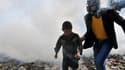 Un homme portant un masque à gaz escorte un enfant dans une rue enfumée d'Alep, en Syrie, le 24 mars 2013.