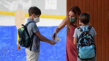 Une enseignante en train de désinfecter les mains d'un élève dans une école près de Séville.