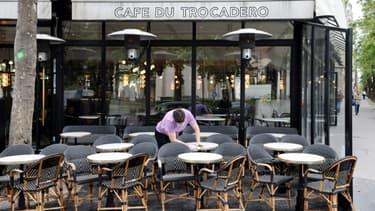 """Un employé nettoie les tables en terrasse au """"Café du Trocadéro"""", le 11 mai 2021 à Paris, avant la réouverture des bars et restaurants le 19 mai"""