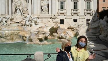 Des touristes portant un masque devant la fontaine de Trevi à Rome, le 25 septembre 2020.