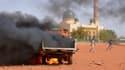 Camion de police en feu à Niamey au Niger, le 17 décembre 2015. En fond, la grande mosquée de la ville.