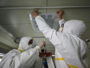 Des employés d'un hôpital de Wuhan scellent une bouche d'aération d'une unité d'isolement le 12 mars 2020, avant la réouverture aux patients non-Covid-19