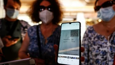 Une femme présente son pass sanitaire à l'entrée d'un restaurant le 22 juillet 2021 au Mont-Saint-Michel