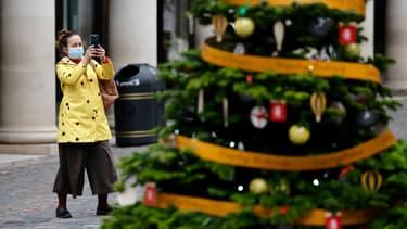Touriste face à un sapin de Noël à Londres.