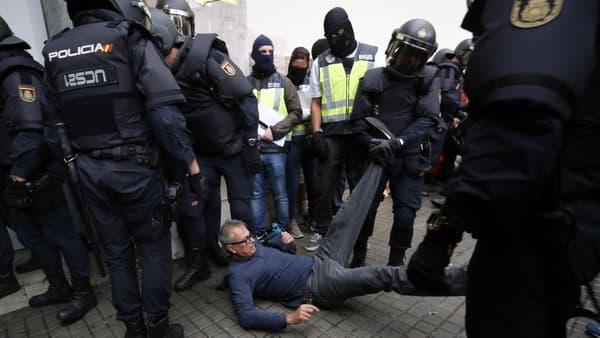 Des policiers emmènent un manifestant de force, devant un bureau de vote, à Barcelone, le 1er octobre.
