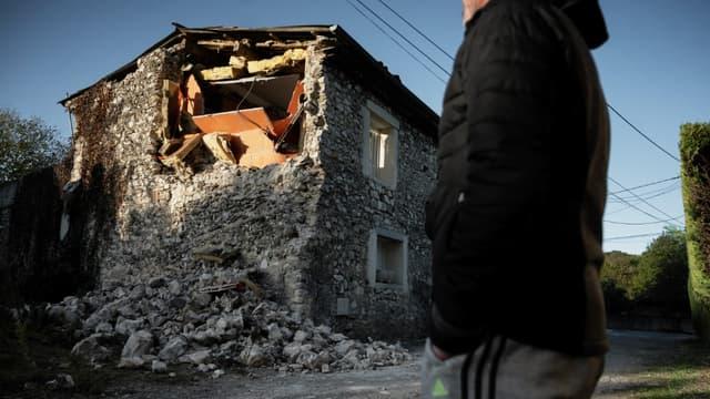 Un résident observe les dégâts du séisme sur une maison, à Teil, le 12 novembre 2019