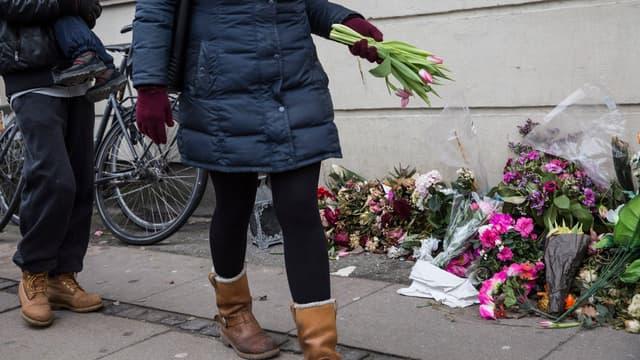 Une femme déposant des fleurs devant l'immeuble où l'auteur présumé de deux attaques meurtrières a été abattu par la police