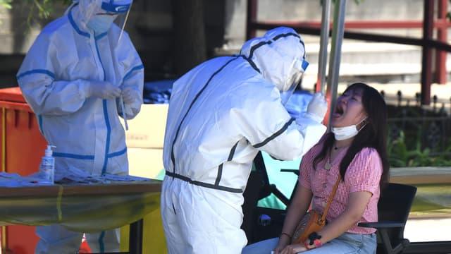 Personnel soignant testant un homme habitant ou étant passé par le marché de Xinfadi ces derniers jours, à Pékin, le 16 juin 2020