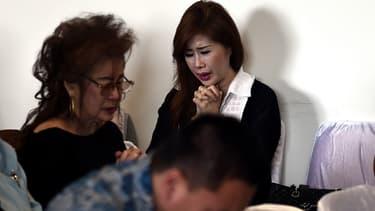 Des proches des passagers portés disparus attendent de leurs nouvelles à l'aéroport de Juanda, en Indonésie.