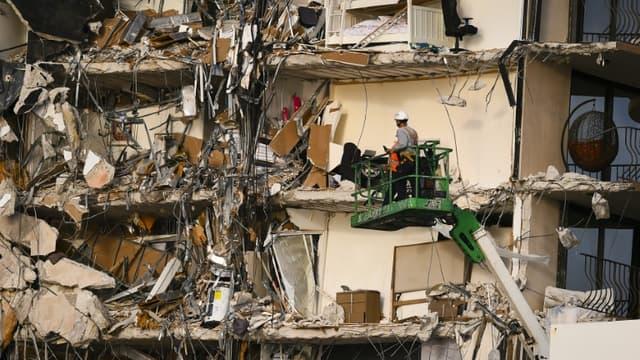 Des secouristes sur une grue devant le reste de l'immeuble qui s'est effondré à Surfside, en Floride, le 25 juin 2021.