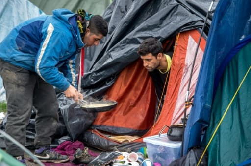 Des hommes se préparent à manger dans le camp de migrants de Grande-Synthe, près de Dunkerque, dans le nord de la France, le 20 octobre 2015