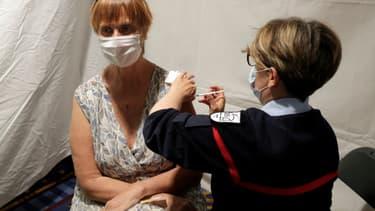 Une femme reçoit une dose du vaccin anti-Covid Pfizer/BioNTech dans le centre de vaccination provisoire mis en place dans le parc d'attractions de Disneyland Paris à Coupvray (Seine-et-Marne), le 24 avril 2021