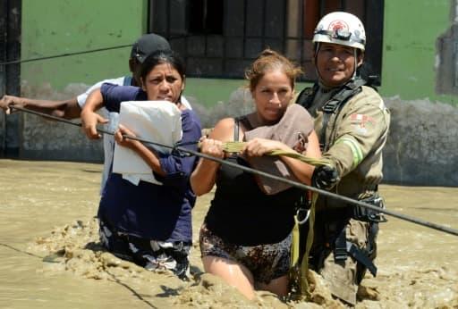 Le 19 mars 2017, des secouristes évacuent des habitants de la commune de Huarmey, cité portuaire à 300 km au nord du Pérou, encerclée par la boue depuis les pluies diluviennes qui ont balayé le pays ces derniers jours