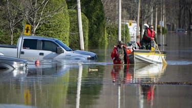 Des policiers canadiens dans une rue inondée de la banlieue de Montréal