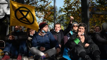 Activistes avec le drapeau Extinction Rebellion bloquant le terminal d'un aéroport à Genève, le 16 novembre 2019