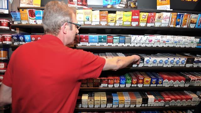 Un buraliste prend un paquet de cigarette dans son rayon, le 04 octobre 2010 à Lille