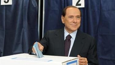 """Silvio Berlusconi dans un bureau de vote milanais, dimanche. Le """"Cavaliere"""" court le risque d'une lourde défaite aux élections locales de dimanche et lundi en Italie où, selon les premiers résultats, sa coalition de centre droit pourrait perdre toute une"""