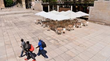 Des passants masqués près d'une terrasse de restaurant désertée à Lérida (Espagne), le 4 juillet 2020