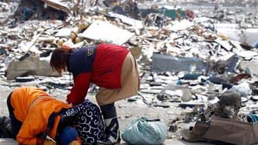 Rescapés du tsunami récupérant des effets personnels dans les ruines de leur maison à Otsuchi. Près d'une semaine après la disparition de leurs maisons emportées par le tsunami, la vie des quelque 1.000 survivants de ce petit port de pêche ne tient toujou