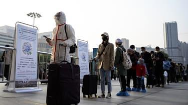 A Wuhan, des personnes font la queue à la gare pour quitter la ville, le 8 avril 2020.