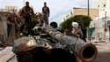 Des insurgés libyens sur un véhicule des forces pro-Kadhafi. Les forces libyennes pro-Kadhafi qui assiègent la cité portuaire de Misrata ont reçu l'ordre de se retirer, a indiqué samedi un soldat libyen blessé capturé par les rebelles qui tiennent toujour