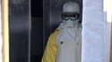 Un homme porte un masque et une combinaison de protection à l'entrée d'une tente médicale à Gueckedou, en Guinée.