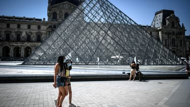 Des touristes masqués devant la Pyramide du Louvre