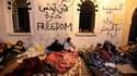 """Manifestants de la """"caravane de la liberté"""" s'apprêtant à passer une deuxième nuit devant les bureaux du Premier ministre, à Tunis. Alors que des manifestants continuent d'exiger le départ du gouvernement d'union tunisien et que le chef de l'armée a lancé"""