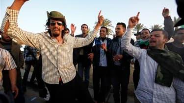 """Des partisans de Mouammar Kadhafi manifestent leur soutien au dirigeant libyen devant le complexe étroitement gardé de ce dernier à Tripoli. La France et la Grande-Bretagne ont appelé lundi les pro-Kadhafi à faire défection """"avant qu'il ne soit trop tard"""""""