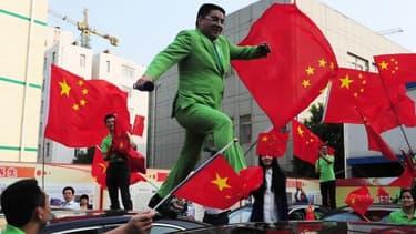Chen Guangbiao, avec costume vert pomme et drapeaux rouges, un excentrique modèle d'écologie à la chinoise.