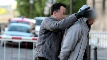 Alexandre D., l'agresseur présumé d'u militaire à La Défense est conduit au palais de justice de Paris par un policier.