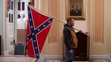 Un partisan de Donald Trump tenant un drapeau confédéré à l'intérieur du Capitole à Washington, le 6 janvier 2021.