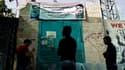 La jeunesse palestinienne debout face à une affiche présentant un portrait de l'auteur présumé de l'attaque contre un bus israélien, le 20 avril 2016.