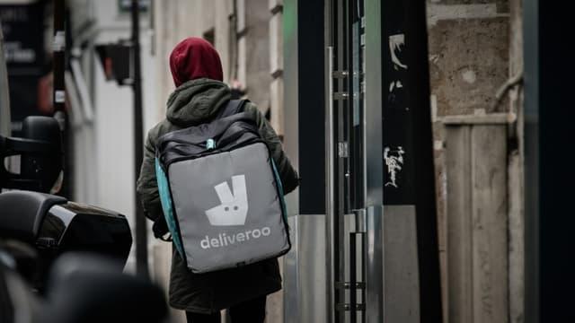 Un livreur pour la plateforme Deliveroo cherche une adresse à Paris, le 8 mars 2020