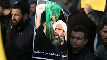 Un Irakien porte le portrait d'un dignitaire chiite Nimr al-Nimr, exécuté par l'Arabie saoudite, lors d'une manifestation le 3 janvier 2016 à Bagdad