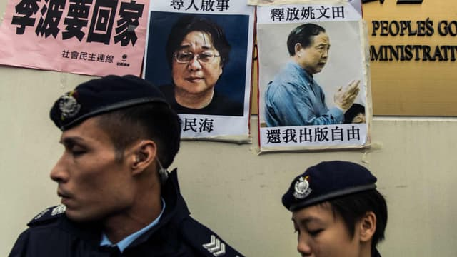 Des policiers passent devant les avis de recherche concernant Gui Minhai (à gauche), un des cinq libraires travaillant pour la maison d'édition Mighty Current, et disparus depuis 2015.