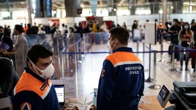 Des membres de la Protection civile contrôlent des voyageurs dans le cadre des mesures sanitaires à l'aéroport Roissy Charles de Gaulle, le 25 avril 2021